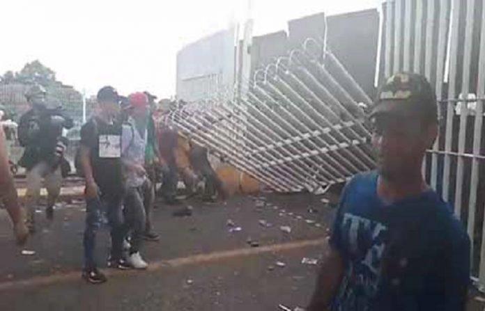 """Miles de migrantes, en su mayoría hondureños, rompieron la valla metálica que separa a Guatemala de México y después de un enfrentamiento con la policía civil, cruzaron hacia territorio mexicano, y con palos, piedras, tubos, entre otros objetos, intentaron atravesar el puente """"Rodolfo Robles"""", donde fueron contenidos por el grupo antimotines, desatando un enfrentamiento con resultado de varios heridos y un muerto de origen hondureño. Mientras tanto, otra caravana procedente de El Salvador se aproxima a la frontera con México."""